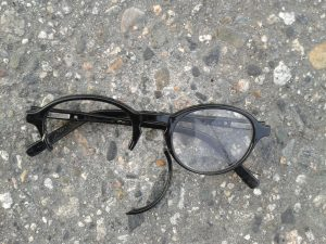 Broken eyeglasses on pavement